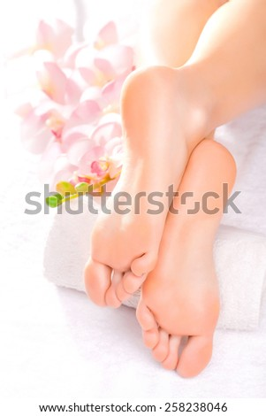 Foot massage in the spa salon with orchid - stock photo