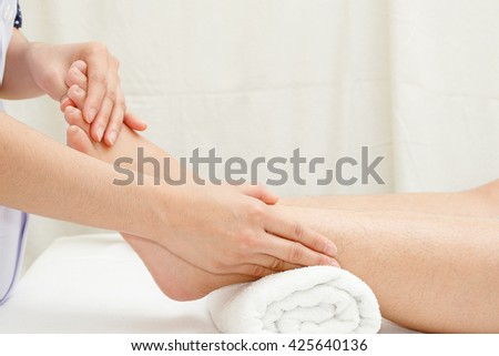 Foot massage, therapist's hands massaging female foot