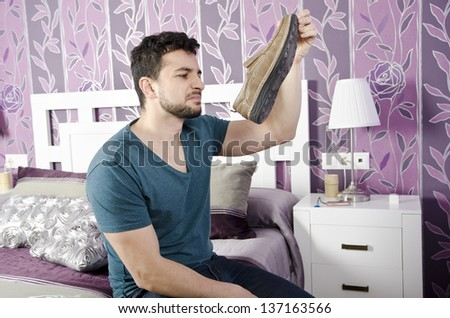 Foot odor. Man smelling a shoe in bedroom.