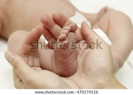 Foot of a baby in his mother's hands. The concept of care of the child