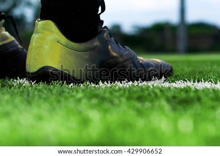 foot of a soccer player or football player on green grass - stock photo