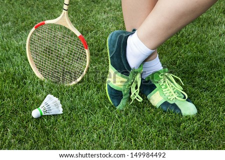 foot of woman who plays badminton on grass - stock photo