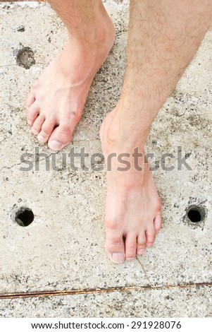 Foot on concrete background