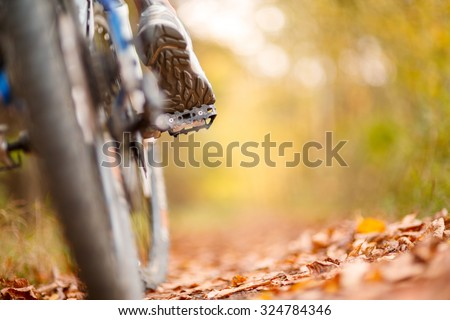 foot on pedal of bicycle in park, active summer. Sunflare at background - stock photo