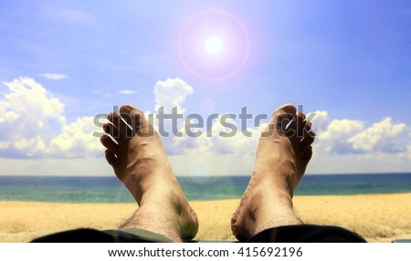 Foot on the beach with bright sunlight - stock photo
