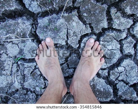 Foot on the ground / cracked ground in drought / background effects of global warming. - stock photo