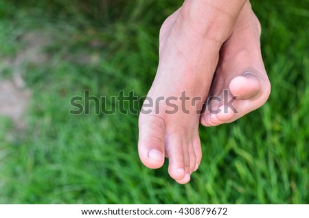 Foot over green grass.Small Little boy  feet in the field.Top view on kid's bare feet . Children feet playing and having fun time on the beautiful - stock photo