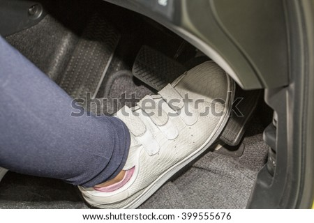 foot pressing the accelerate pedal of a car