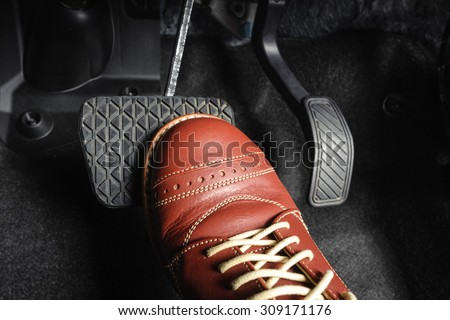 foot pressing the brake pedal of a car - stock photo