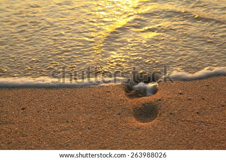 foot print in sand washed by wave - stock photo