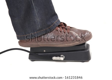 Foot pushing musical wah-wah pedal. Isolated on white background.