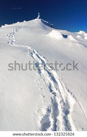 Foot steps in the snow, climbing toward mountain top - stock photo