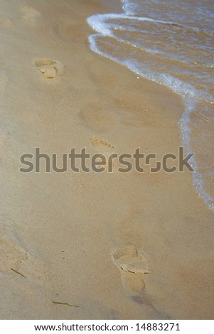 Foot steps on sand - stock photo