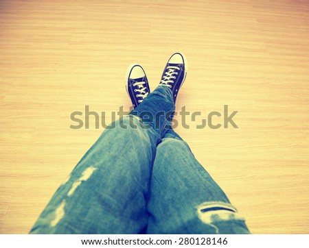 Foot teenager in jeans and classic sneakers - a top perspective view. Photo toned in yellow style instagram - stock photo