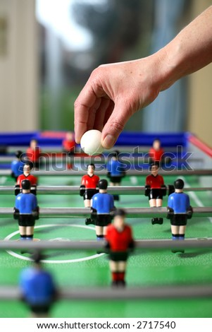 Football about to be dropped to start the game of table football - stock photo