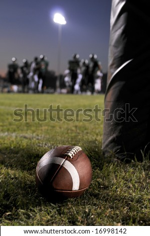 Football at the field with an ongoing game as background - stock photo