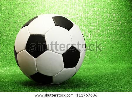football ball on artificial green grass - stock photo