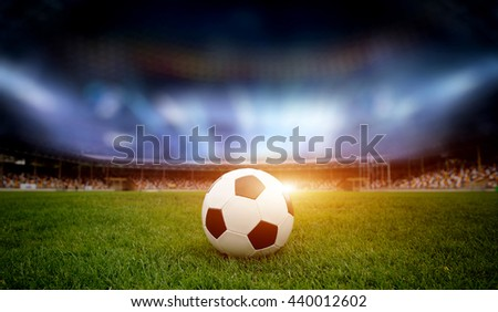 Football ball on the field of stadium with light - stock photo