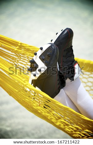 Football boots close-up of soccer player relaxing in beach hammock - stock photo