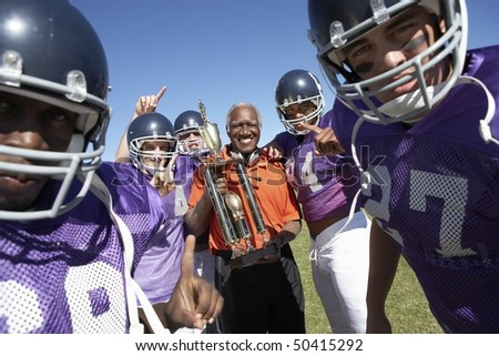 Football Coach and Players holding trophy on field, portrait, (portrait) - stock photo