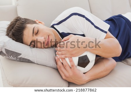 Football fan sleeping on couch hugging ball - stock photo