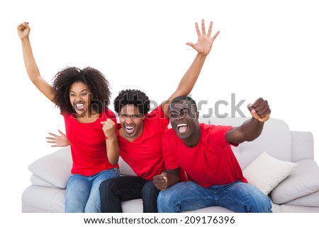 Football fans in red cheering on the sofa on white background - stock photo