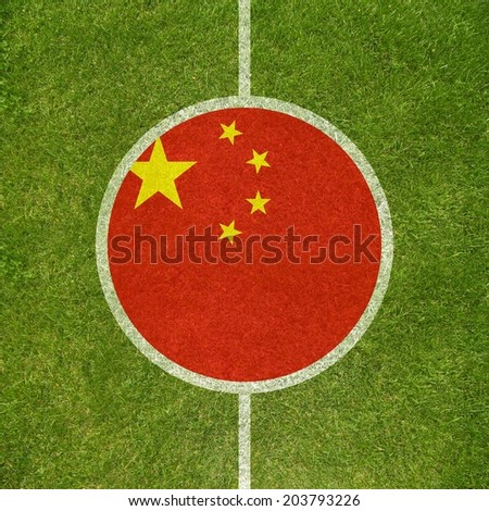 Football field center closeup with Chinese flag in circle  - stock photo