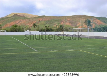 Football field  in beautiful landscape. In hte sports stadium of Haria, Lanzarote, Canary Islands, Spain. - stock photo