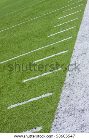 Football field sideline showing yard markers on artificial turf.