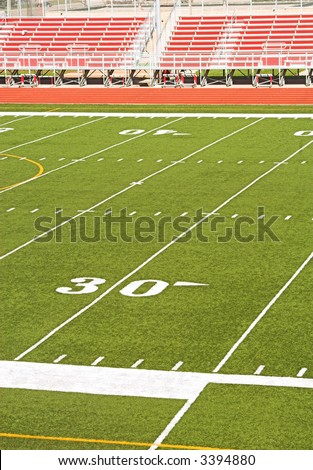 Football field viewed from high angle - red bleachers in background. - stock photo