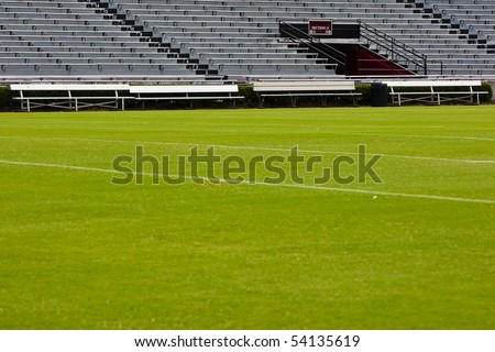 Football field with empty bleachers in the background. - stock photo