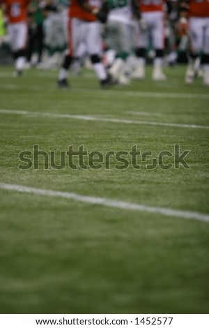 Football field with players at distance, shallow DoF - stock photo