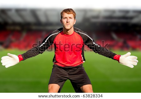 Football goalkeeper at the stadium ready to catch a ball - stock photo