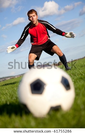 Football goalkeeper ready to catch the ball outdoors - stock photo