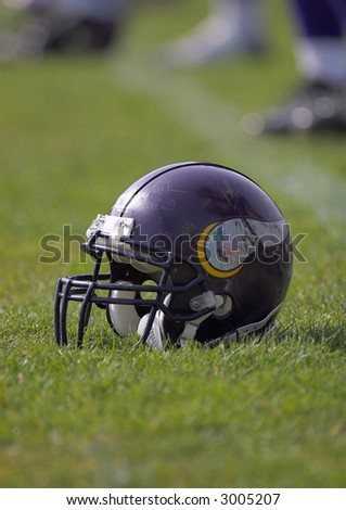 Football helmet placed on the playing field. - stock photo
