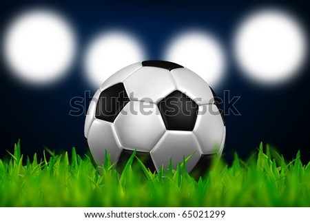 football in the green grass on spotlight background