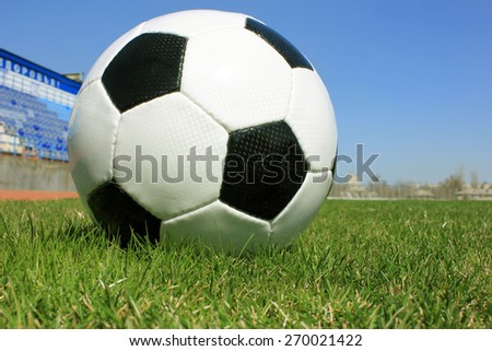 Football on a grass lawn of sports stadium - stock photo