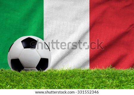 Football on grass field with wave flag of Italy