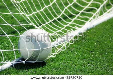 football on grass with net - stock photo