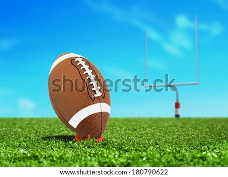Football on Kicking Tee with Goal Post - stock photo