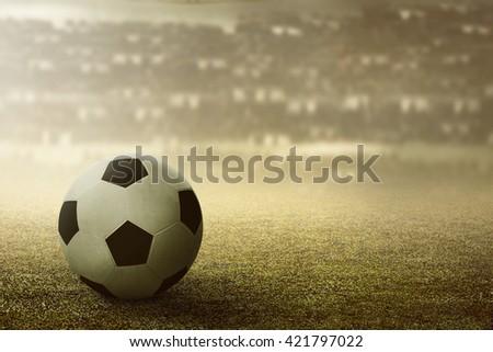Football or soccer ball on football stadium grass - stock photo