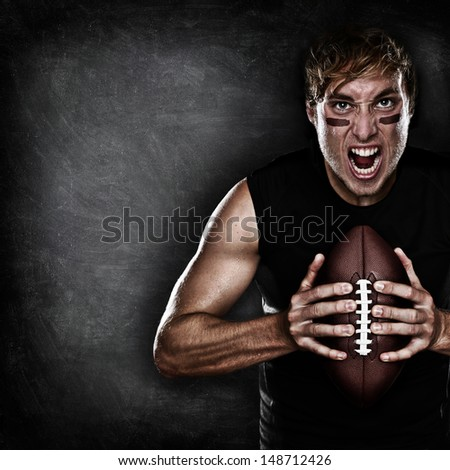 Football player aggressive portrait holding american football on black blackboard background with copy space for text or design. Caucasian male model in his 20s. - stock photo