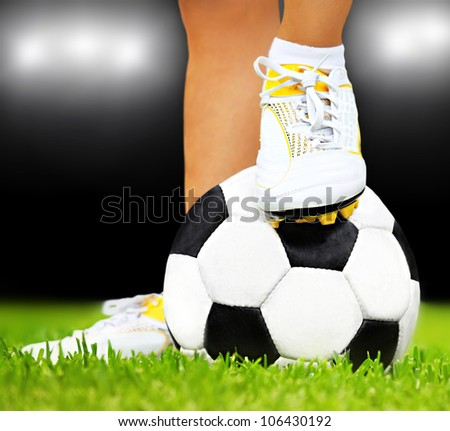 Football player feet on the ball, playing sport outdoor at night stadium, conceptual image of competition & game - stock photo