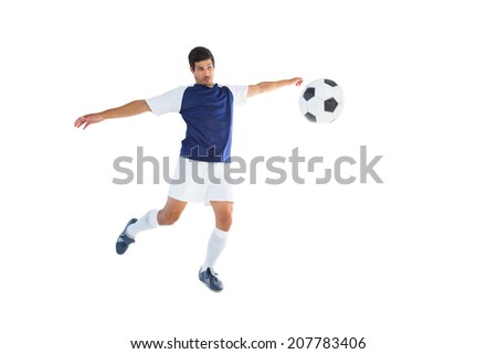 Football player in blue kicking ball on white background