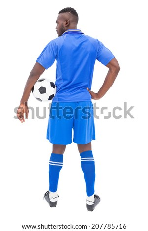 Football player in blue standing with ball on white background