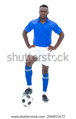 Football player in blue standing with the ball on white background