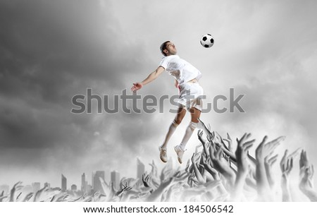 Football player in jump kicking the ball supported by fans - stock photo