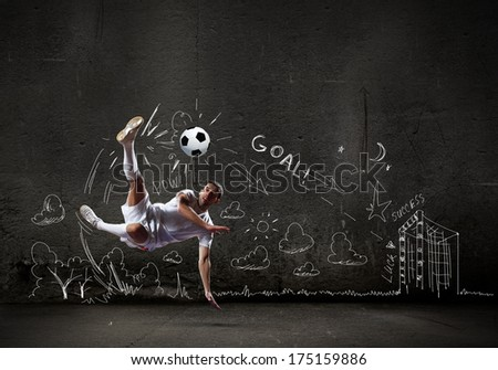 Football player in jump striking ball with sketches at backdrop - stock photo