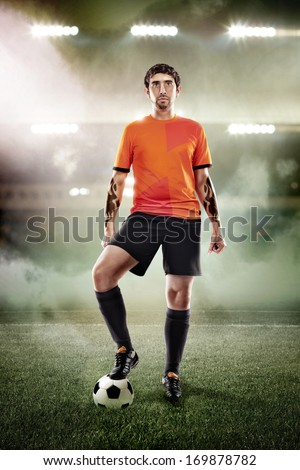 football player in orange shirt with ball at the stadium - stock photo
