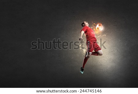 Football player in red shirt jump taking ball - stock photo